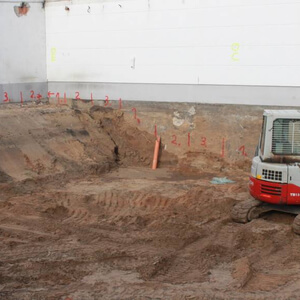 The bottom plate of the new building will be a lot deeper in the earth as the one of the old and bordering building. To prevent the old building from collapsing the excavation works have to be done in a certain order – therefore the red numbers on the wall…