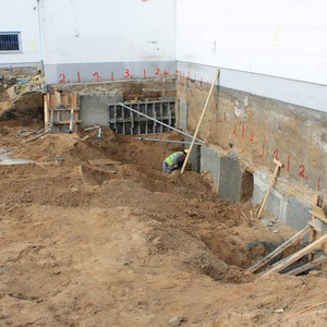 Next to the wall of the bordering building first concrete works for a stable baseplate are made…