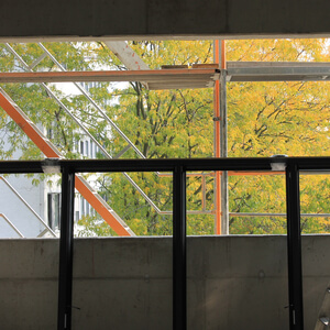 Fall approaches – tree leaves turn golden, seen from the construction site…